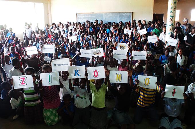 「ZIKOMO!=ありがとう」のメッセージを掲げる子どもたち