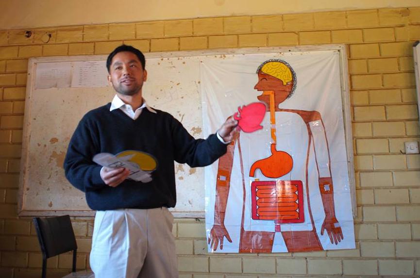 教材を使って体の仕組みを説明する駐在員